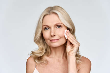 Portrait of woman holding cotton pad doing everyday routine makeup removing.
