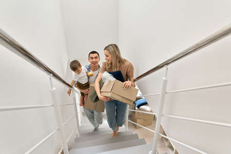 Happy family with child new home owners carrying boxes going upstairs.