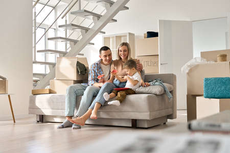 Happy family couple with kid son relaxing on couch on moving day in new home. 免版税图像