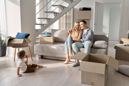 Happy family new home owners with child relaxing on sofa on moving day.