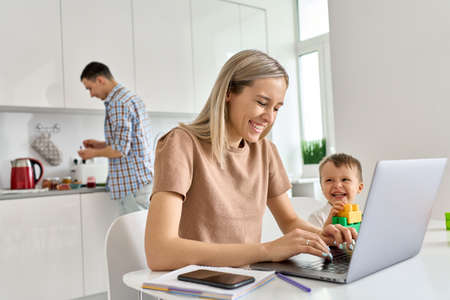 Happy mom working at home using laptop while funny kid son playing.