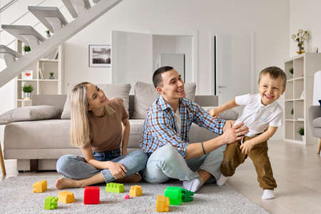 Happy young family couple having fun playing with cute toddler kid son at home.