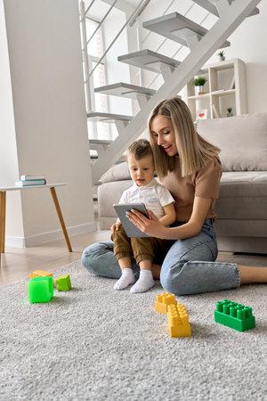 Smiling mum teaching toddler child son using digital tablet at home.
