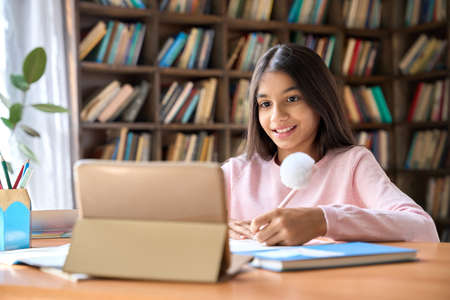 Happy latin schoolgirl watching online learning video at home on tablet.