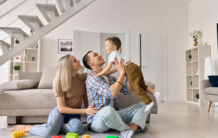 Cheerful family couple playing with happy kid boy in modern living room.