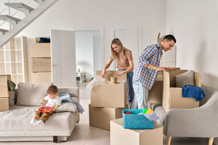 Happy family new home owners with child unpacking cardboard boxes on moving day. 免版税图像