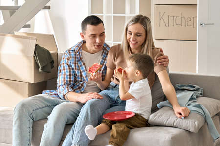 Happy family new tenants with kid sitting on couch at new home at moving day. 免版税图像