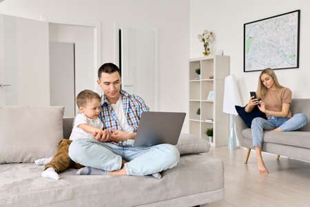 Young family with kid at home watching online classes, surfing social media.