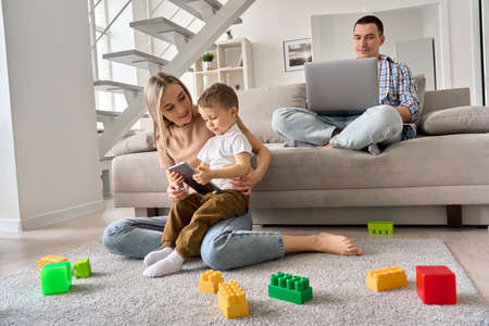 Young family at home, mom and kid watching video on tablet, dad working on pc. 免版税图像
