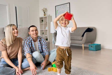 Happy young family with child at home sitting on floor enjoying time together.
