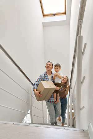 Happy family with child son carrying boxes going up stairs into new home. 免版税图像
