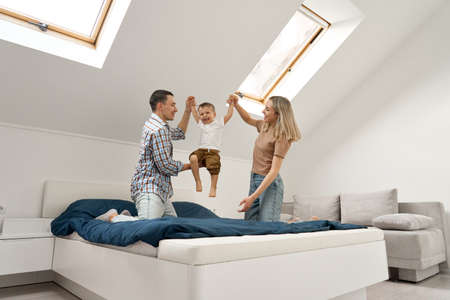Happy family playing with small toddler kid son together in bedroom at home.