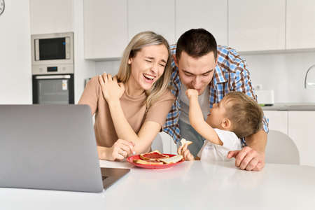 Happy young family with kid son having fun eating toasts in kitchen.