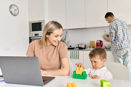 Happy mother working from home using laptop sitting at table with cute kid son.