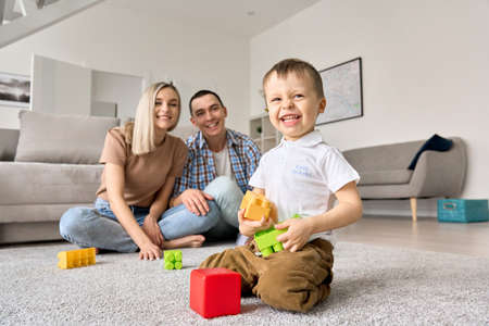 Cute happy kid toddler son playing toys with young parents at home. 免版税图像