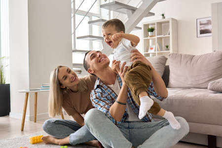 Happy young family couple having fun playing with cute child son at home.