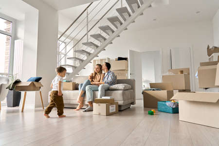 Happy family relaxing on couch on moving day with kid son playing in new home .
