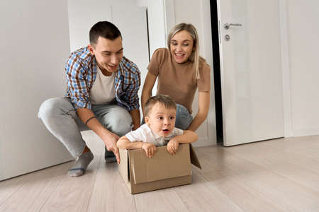 Funny excited child son riding in box on moving day with parents in new home. 免版税图像