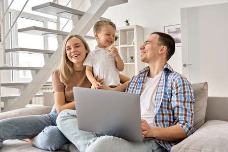 Happy family mom, dad and cute child son having fun using laptop at home.
