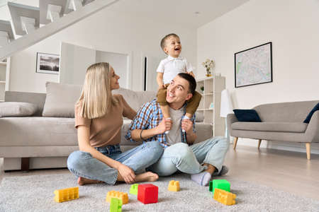 Happy family with toddler child son enjoying spending time together at home.