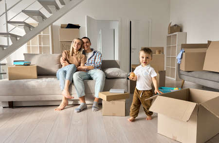 Happy family new home owners with child son in living room on moving day.