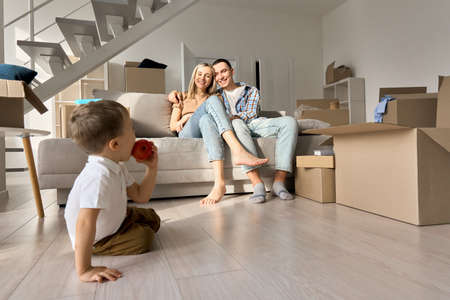 Happy family couple with kid son relaxing on moving day in new home living room.