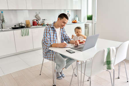 Young dad sitting in kitchen at home with kid watch education classes on pc.
