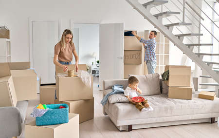 Young couple with kid at home unpacking boxes after relocating. 免版税图像