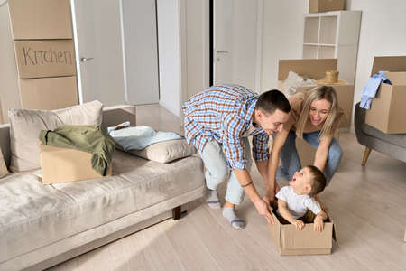Happy parents pushing carton box with kid in new mortgage apartments. 免版税图像