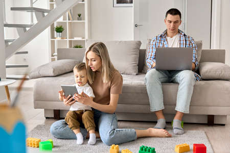 Young family at home, mom and kid watching movies on tablet, dad working on pc.