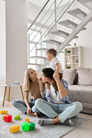Young family with boy on dads neck sitting on floor in modern living room. 免版税图像