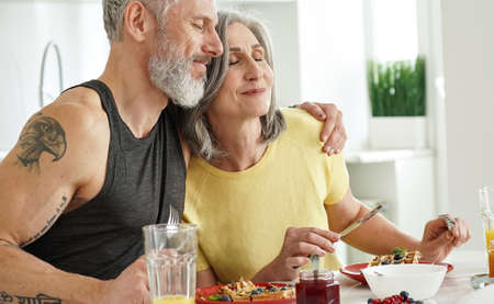 Happy mature husband embracing older wife enjoying having breakfast at home. 免版税图像