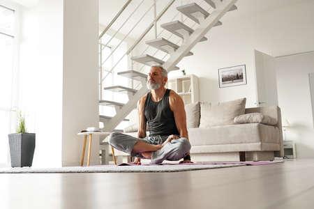 Strong older mid aged tattooed yogi man doing yoga exercises at home.
