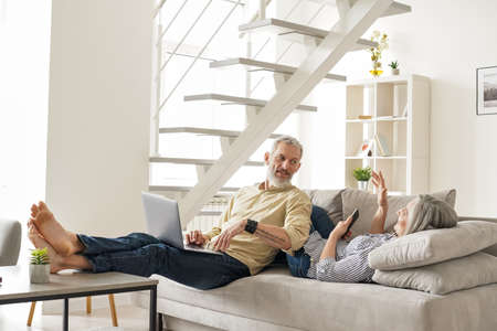 Happy mature older couple talking using devices relaxing at home on couch.