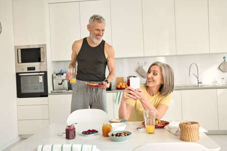 Happy older mature family couple having breakfast using phone in kitchen.