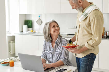 Senior husband preparing breakfast to happy wife working from home office.