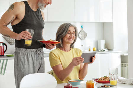 Happy older mature family couple having breakfast using tablet in kitchen.