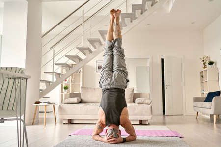 Fit middle aged senior tattooed man doing headstand yoga exercise at home.