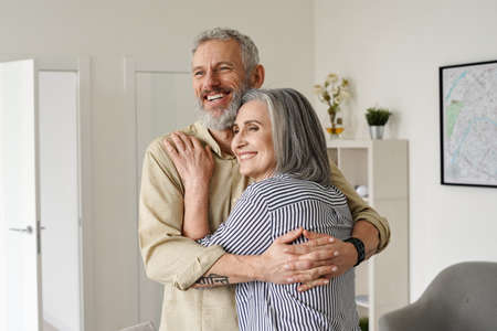 Happy mature couple hugging, looking away, thinking, dreaming of future at home.