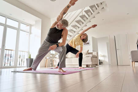 Fit middle aged family couple doing fitness morning exercise at home.