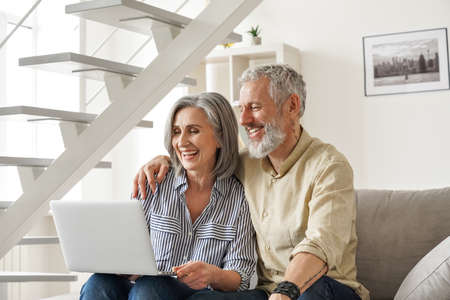 Happy older mid age couple using laptop computer sitting on couch at home.