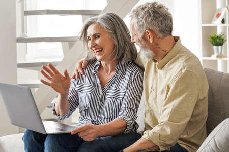 Happy mature old couple waving having virtual meeting on laptop at home. 免版税图像