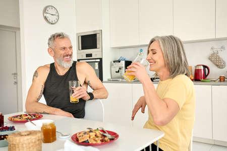 Happy healthy fit senior family couple having breakfast sit at kitchen table. 免版税图像
