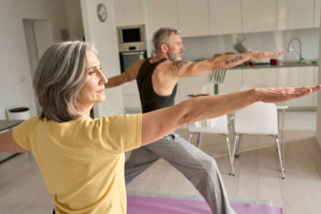 Fit middle aged family couple doing warrior yoga exercise at home.
