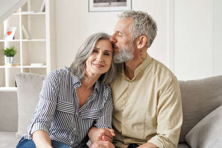 Happy affectionate classy older mature couple bonding with eyes closed at home.
