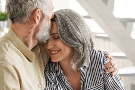 Happy affectionate mature husband embracing kissing wife enjoying tenderness.