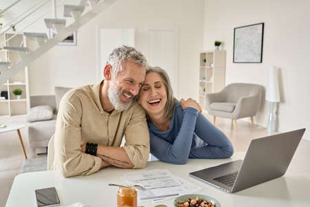 Happy mature older couple laughing, bonding sitting at home table with laptop. 免版税图像