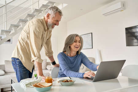 Happy middle aged couple having fun using laptop computer at home.