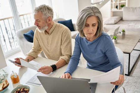 Mature couple reading documents bills paying bank loan using laptop and phone.