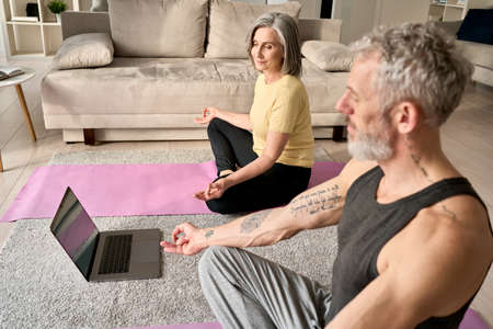 Happy mature old couple doing yoga meditating together at home with laptop. 免版税图像